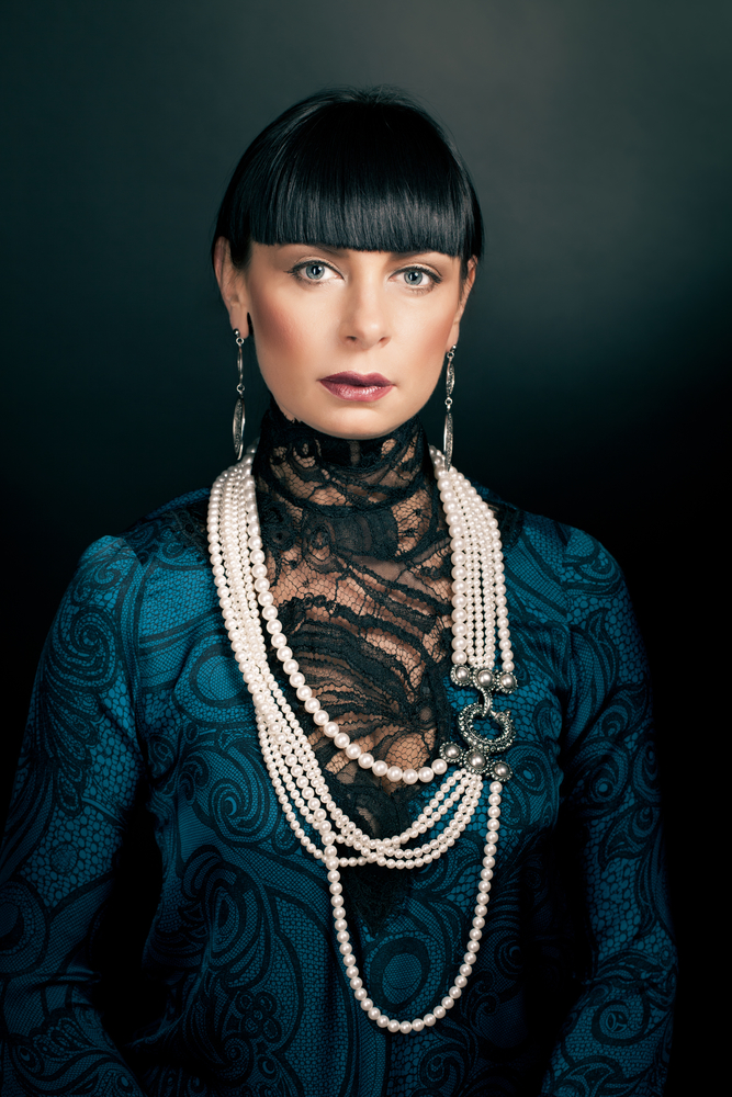 Glamour portrait of woman wearing green blouse with pearl beads